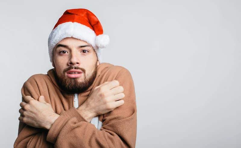 Homme en pyjama avec un bonnet de père Noël sur la tête