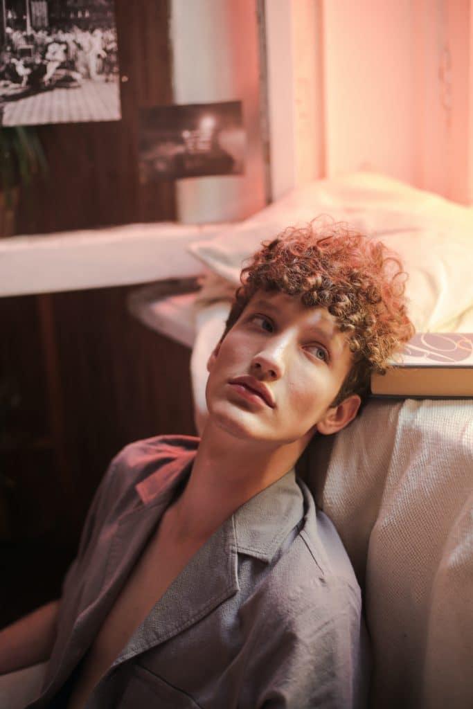 homme pyjama adossé contre lit