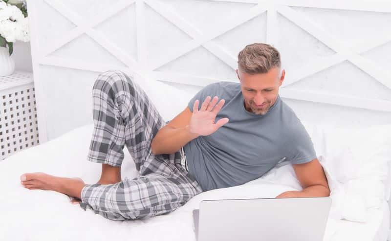 Homme sur son lit en pyjama avec un ordinateur